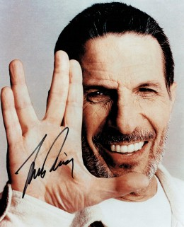 An 8x10 of an older Leonard Nimoy, not in character, holding his hand in the traditional Vulcan greeting gesture. It is autographed by Nimoy.