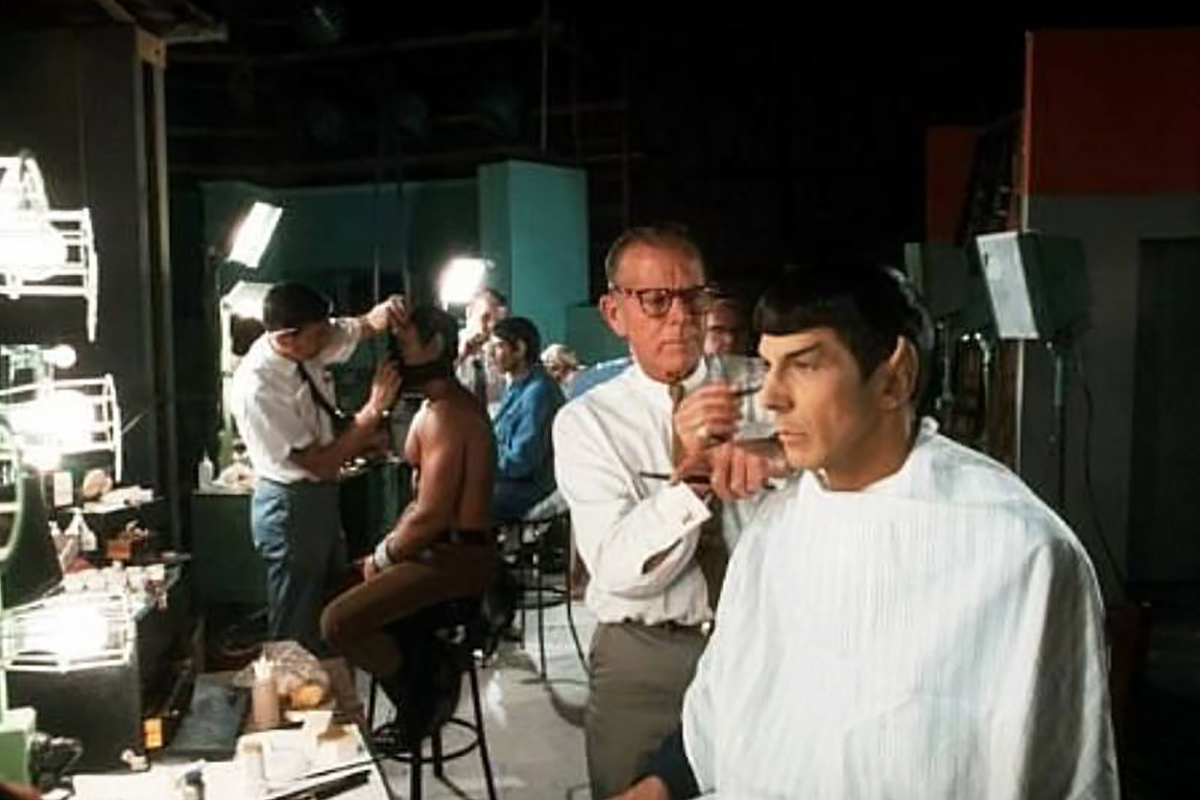 Make-up man Fred Philips at work on Spock, in preparation for filming Amok Time. The photo is in colour and shows Phillips, Leonard Nimoy, plus other make-up artists and actors in the background.