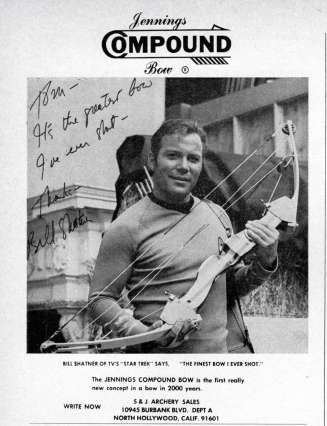 William Shatner in his Star Trek uniform, holding a compound hunting bow.