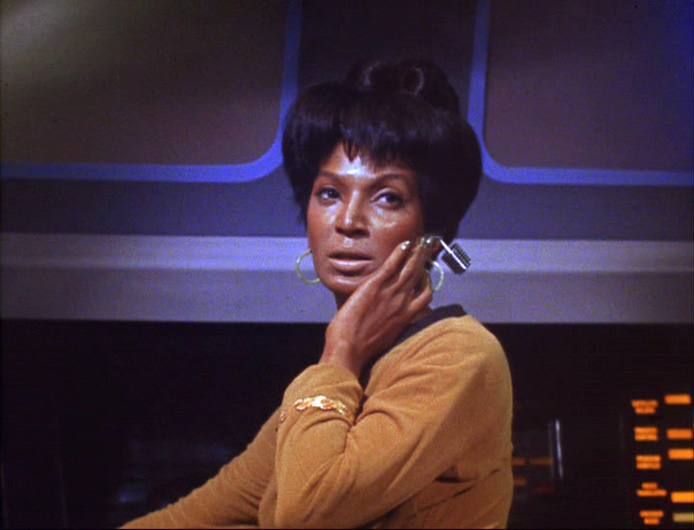 A photo of Uhura standing at her console, from The Corbomite Maneuver. She is using an earpiece designed by Irving Feinberg.