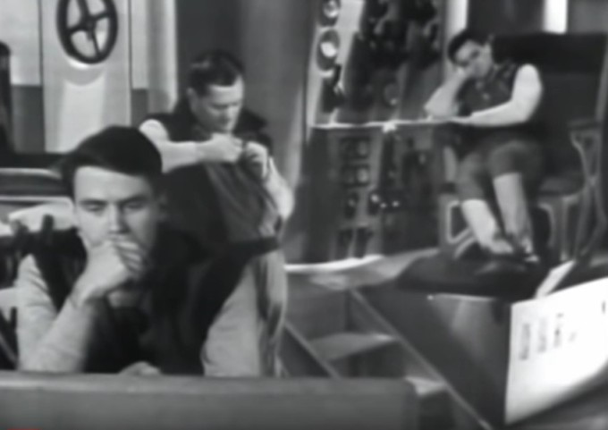 A screen cap from the TV show Space Command, showing James Doohan and two other actors on the bridge. Doohan's character is shown to be asleep at his station.