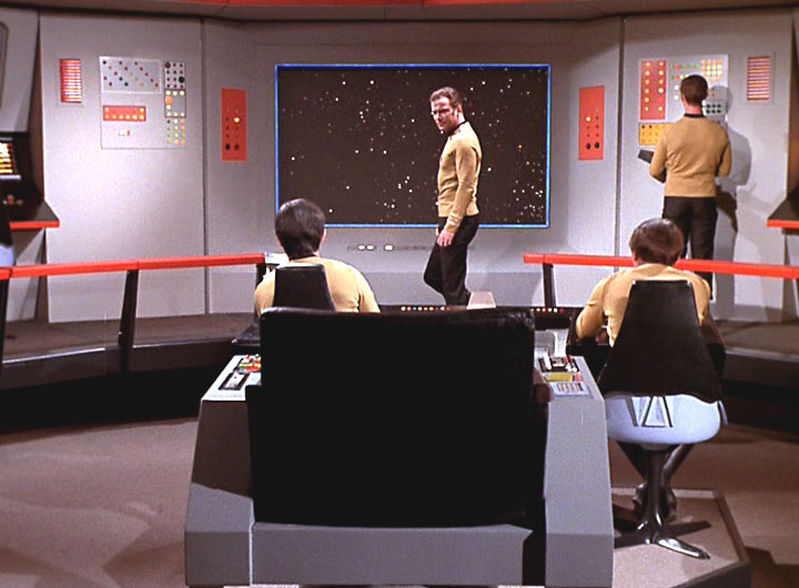 A screen cap from the Star Trek episode Spock's Brain, featuring Captain Kirk walking in front of the large central view screen