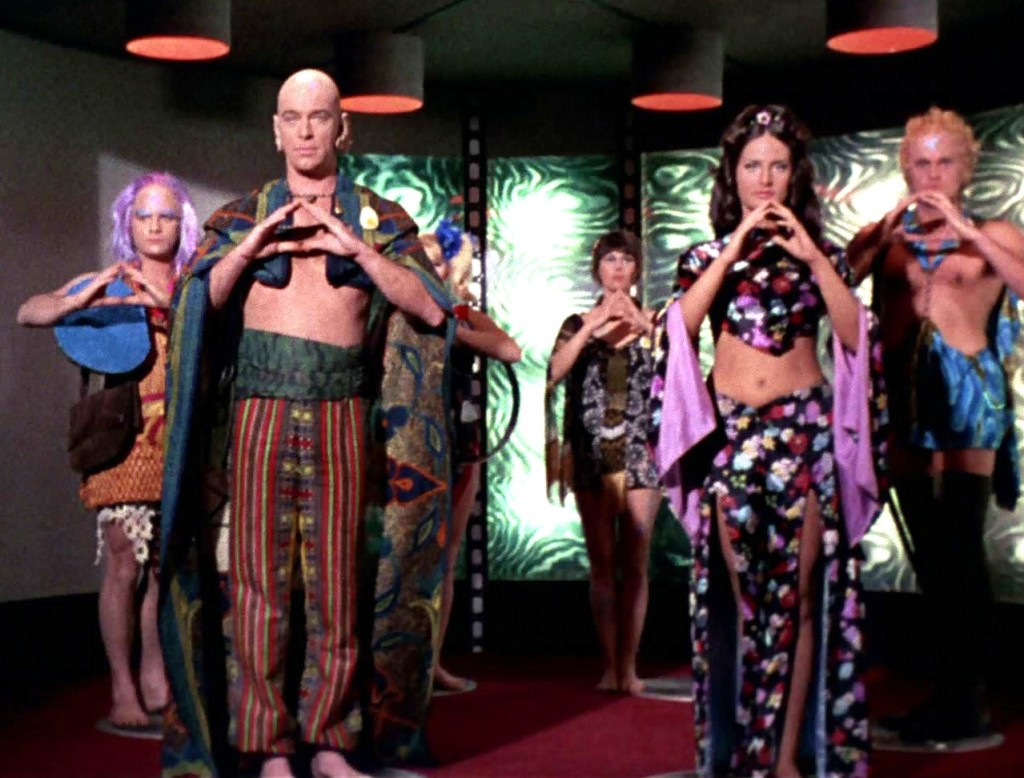 Dr. Sevrin and his followers stand in the Enterprise transporter room, holding their hands in front, forming triangles, in the One gesture of their faith.