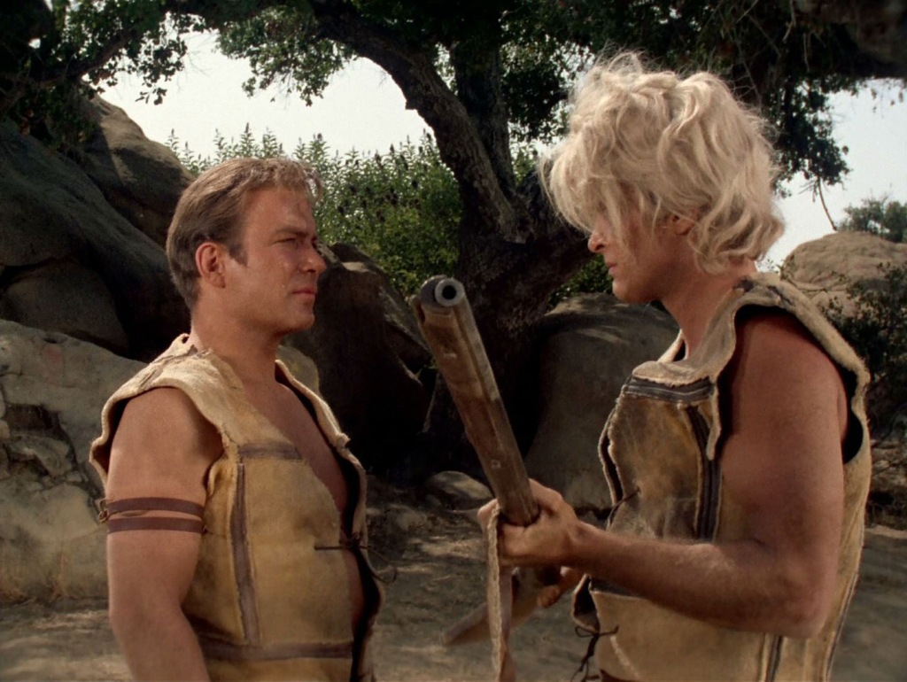 A screencap from the Star Trek episode A Private Little War, showing a standing Captain Kirk and the villager Tyree. Tyree is holding a flintlock gun and demanding that Kirk send him more.