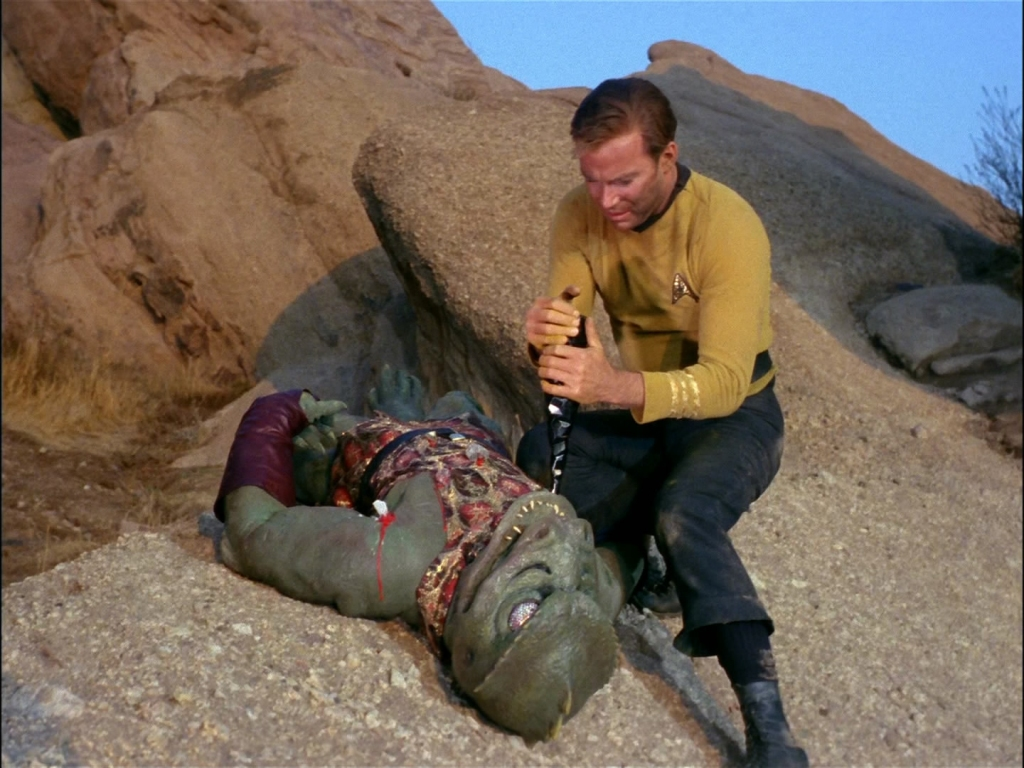 A screencap from the Star Trek episode Arena, in which Kirk has defeated the lizard-like Gorn in combat and kneels over the unconscious foe. Kirk holds a sharp rock but is hesitating before killing his adversary.