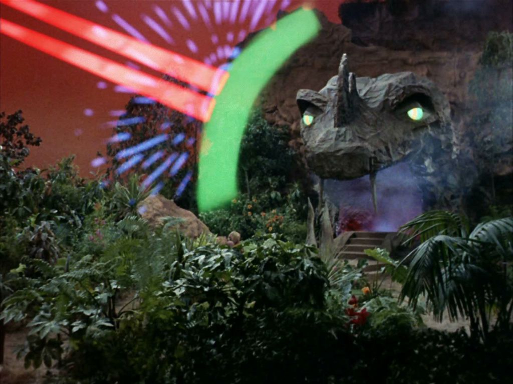 A screen cap from the Star Trek episode The Apple, showing the snakelike statue of Vaal being hit by the Enterprise's phasers