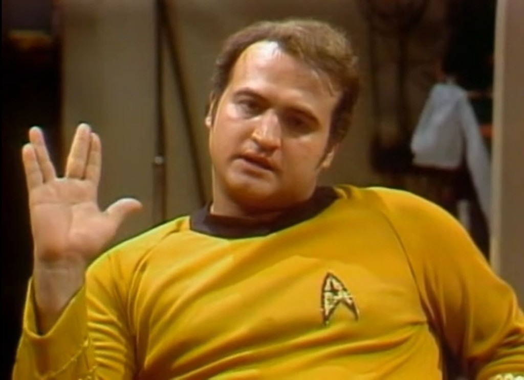 Actor John Belushi, dressed as Captain Kirk, giving the Vulcan salute