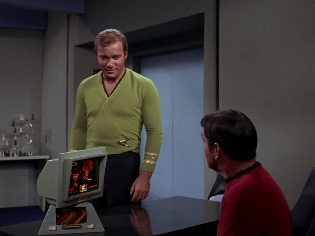 A scene from the Star Trek episode The Trouble with Tribbles. Kirk, standing, is speaking with a seated Scotty. On the screen in front of Scotty is an engineering schematic.