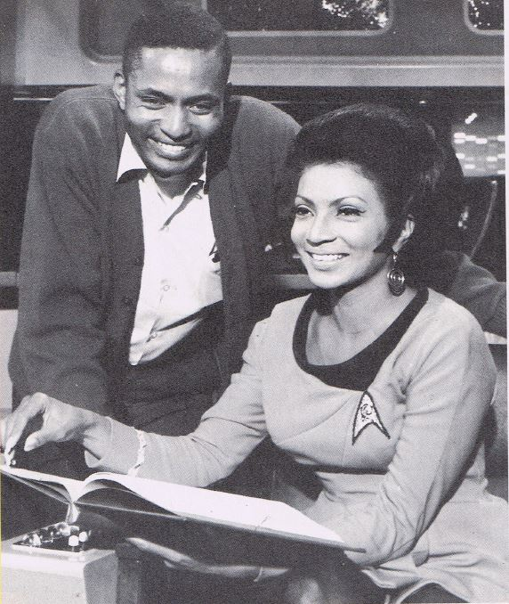 A photo from the Starlog article Charlie Washburn wrote. In the photo, Washburn leans over Nichelle Nichols, sitting in the captain's chair, as she reviews a script.