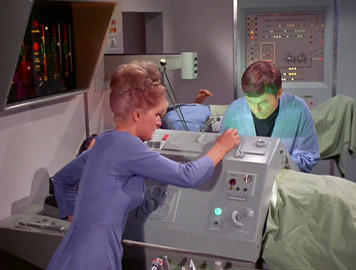 A screencap from the Star Trek episode Journey to Babel, showing McCoy leaning over the biobed, operating on Sarek. His face is illuminated by green light.
